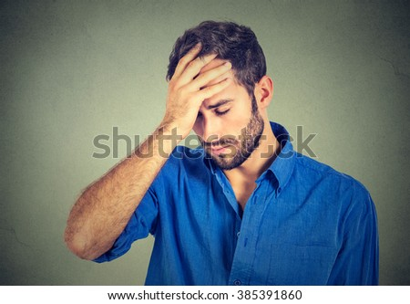 portrait stressed sad young man looking down isolated on gray wall background  - stock photo