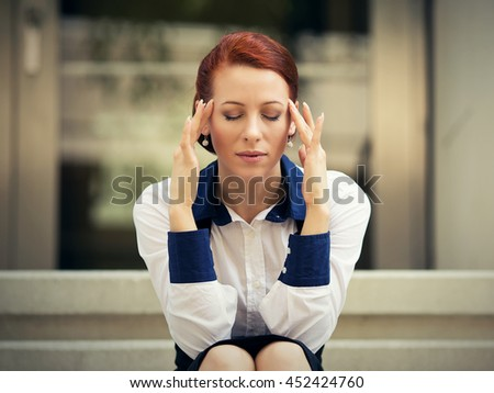 portrait stressed sad young woman sitting outdoors having headache. City urban life style stress