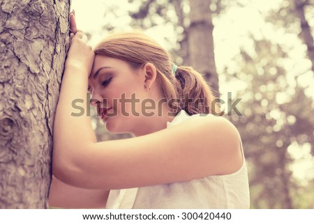 portrait stressed sad young woman standing outdoors on summer day in park  - stock photo