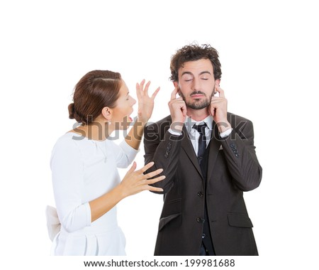Portrait stressed young couple going through hard times in relationship, isolated white background. Upset angry wife, girlfriend trying to explain something to annoyed man closes ears, eyes ignoring