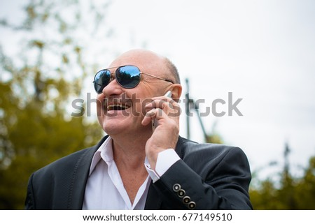 Portrait Stylish Mature Men In White Shirt And Jacket And Blue Sunglasses  Using Smart Phone.