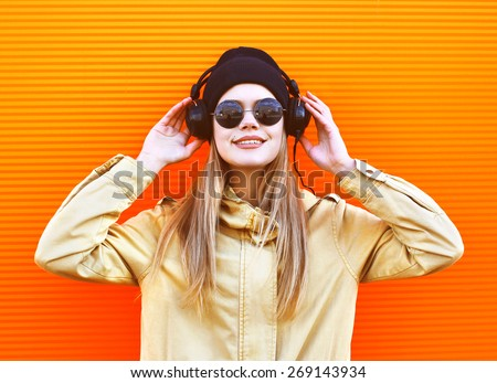 Portrait stylish woman wearing a black hat and headphones listens to music enjoys freedom, cool hipster girl in the city against a colorful orange wall, street fashion concept, urban style - stock photo