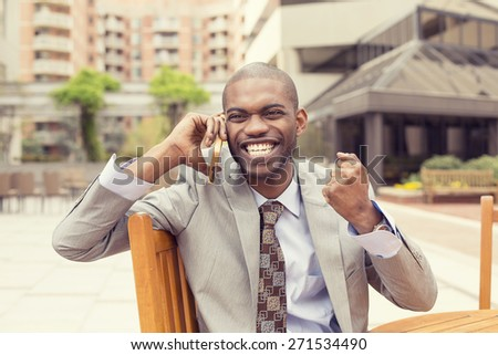 Portrait successful man talking on mobile phone receiving good news fist pumped celebrating success outside city background. Positive human emotion facial expression. Life perception achievement - stock photo