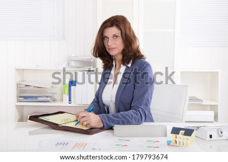 Portrait: Successful older business woman sitting in her office.
