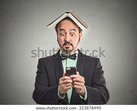 Portrait surprised business man funny looking corporate executive reading news on smart phone holding mobile book over head isolated grey wall background. Human face expression emotion reaction - stock photo
