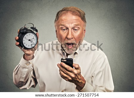 Portrait surprised business man with alarm clock looking at smart phone with funny face expression late for meeting isolated grey wall background. Human face expression emotions, feelings - stock photo