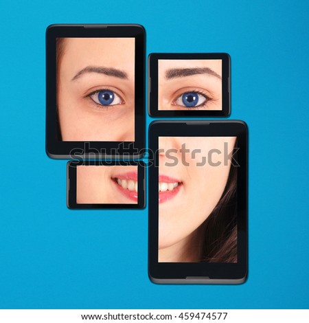 Portrait teenage girl on tablet pc and smart-phone lying side by side isolated on blue background with soft shadow