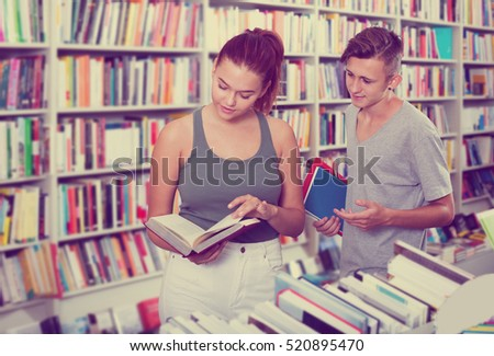 Portrait teenager girl and boy holding open textbook in hands in book store