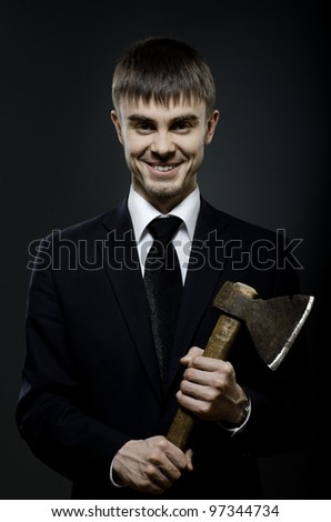 portrait  the  beautiful  businessman  in black costume and black necktie with axe, sinister look and smile