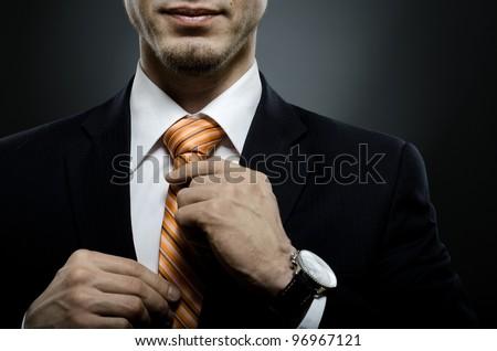 portrait  the  beautiful  businessman  in black costume tie one's necktie - stock photo