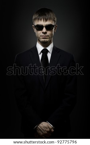 portrait  the  beautiful  man in black costume,  special-service agent or  body guard