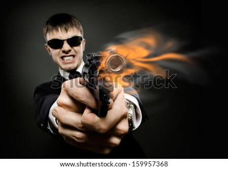 portrait  the  beautiful  man in black costume,  special-service agent or  body guard with  pistol - stock photo