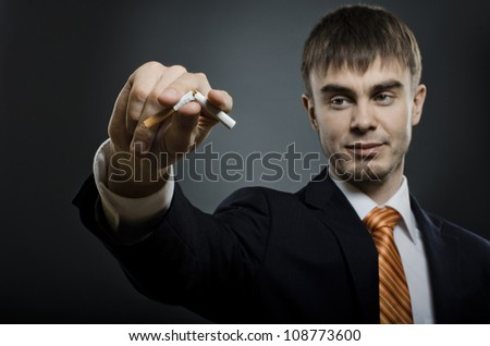 portrait  the   businessman in costume give up cigarette. no smoking - concept