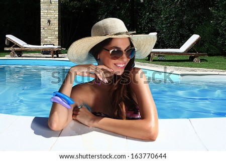 portrait the cute brunette in swimming pool with straw hat sunglasses - stock photo