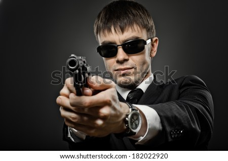 portrait the  man in black costume,  special-service agent or  body guard with  pistol - stock photo