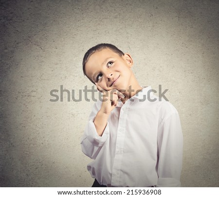 Portrait thinking, daydreaming child, boy imagining future, finger on face, looking up, isolated grey wall background. Positive human facial expression, emotion, feeling life perception, body language - stock photo