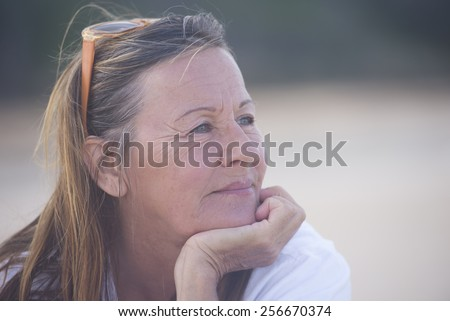 Portrait thoughtful attractive senior woman, laid back and relaxed chin on hand, peaceful confident outdoor, blurred background and copy space. - stock photo