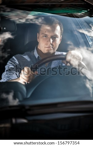 Portrait through glass of handsome driver - stock photo