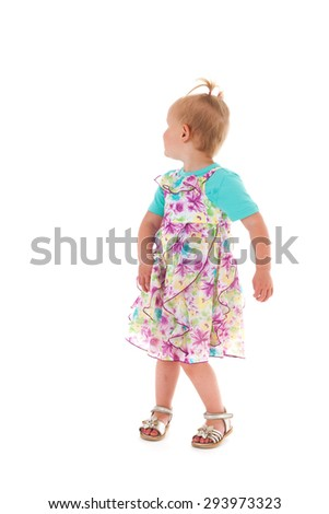 Portrait toddler girl standing in studio and looking back