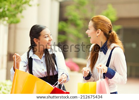 Portrait two happy, laughing young women showing each other what they bought in shopping mall, isolated outdoor street background. Positive human emotions, feeling, face expressions, lifestyle - stock photo