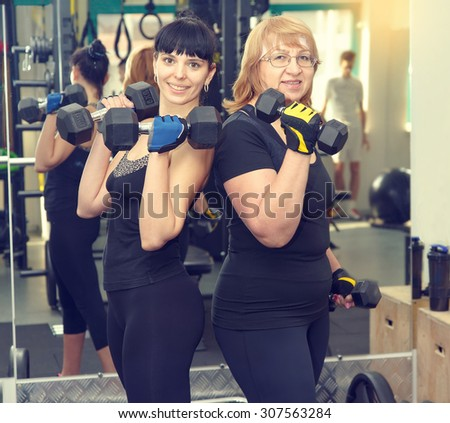 Portrait two women is engaged in a sports hall. Toned image. Women holding a dumbbell for fitness. Sporting women. Sports and fitness a lifestyle in all age. Pretty mature women. Client fitness club. - stock photo