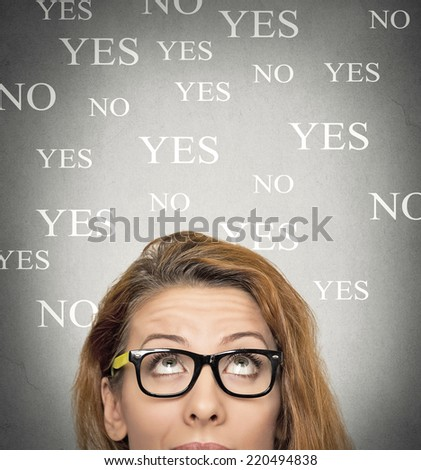 portrait undecided uncertain woman looking up, grey wall background with yes no choices text. Human face expressions, emotions, feelings. Decision choice making process concept - stock photo