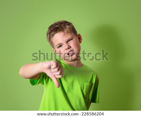 Portrait unhappy, angry, displeased child giving thumbs down hand gesture, isolated on green background. Negative human face expressions, emotions, feelings, attitude, life perception, body language. - stock photo