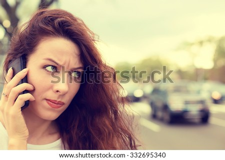Portrait unhappy angry young woman talking on mobile phone looking frustrated standing outdoors on a busy city street. Human face expression, emotion, bad news reaction - stock photo
