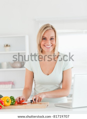 Portrait up of a young woman looking into camera in the kitchen