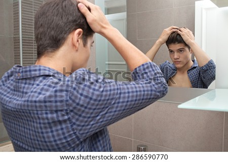 Portrait view of a young teenager man looking at himself in a home bathroom mirror doing his hair and getting ready for college in the morning, home interior. Male care and grooming, indoors. - stock photo