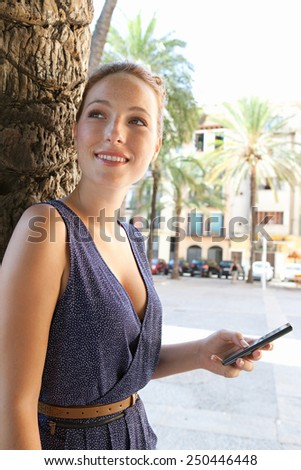 Portrait view of a young tourist woman visiting a picturesque square in a destination city, using a smartphone mobile phone to connect on line on a summer holiday. Travel and technology lifestyle.