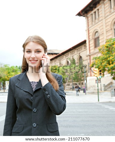 Portrait view of an attractive smiling young professional businesswoman using smartphone to make a phone call in a city with classic buildings, outdoors. (Business, People, Technology) - stock photo