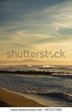 portrait view of atlantic ocean with mountain la rhune in the back in sunset, capbreton, france - stock photo