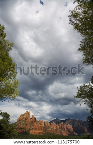 Portrait view of The Red Rocks of Sedona, framed with trees and shrubbery and storm cloud patterns - stock photo