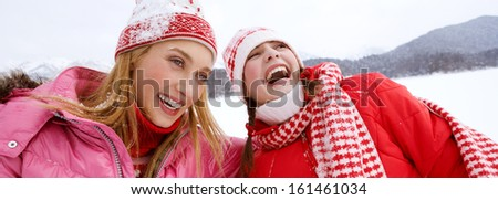 Portrait view of two joyful young women friends having fun and laughing while skiing in a white snow landscape scenery in the mountains, laughing with big expressions, outdoors. - stock photo