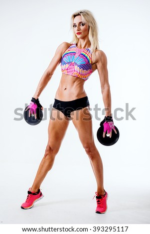 Portrait woman doing workout while holding dumbbell isolated on white background. Blond woman