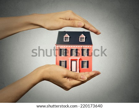 Portrait woman hands presenting small model of house, isolated grey wall background. Real estate, mortgage, home ownership concept. Safety, strong family idea. Insurance, protection - stock photo