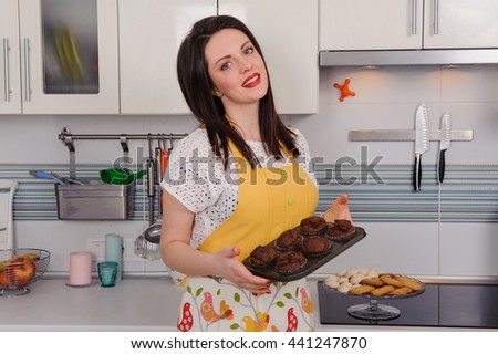 portrait woman in apron with cupcakes in kitchen