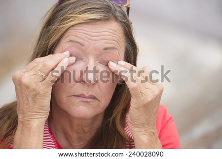 Portrait worried and stressed mature woman with closed eyes and sad expression, wrinkles, outdoor blurred background and copy space. - stock photo