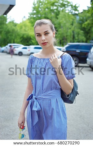 portrait 20-year-old woman in white and blue striped dress  on the background of cars