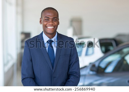 portrait young african businessman in car showroom - stock photo