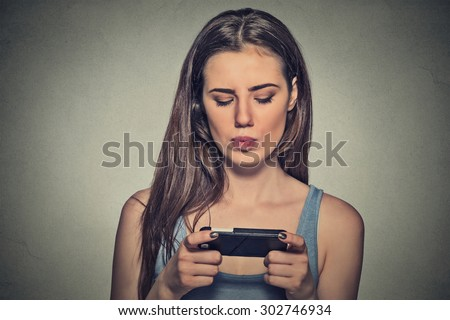 Portrait young angry woman unhappy, annoyed by something, someone on her cell phone texting, receiving bad sms text message news isolated gray wall background. Human face expression emotion reaction - stock photo