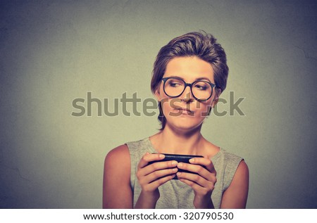 Portrait young angry woman with glasses unhappy, annoyed by something on cell phone while texting receiving bad sms text message isolated grey wall background. Human face expression emotion reaction - stock photo