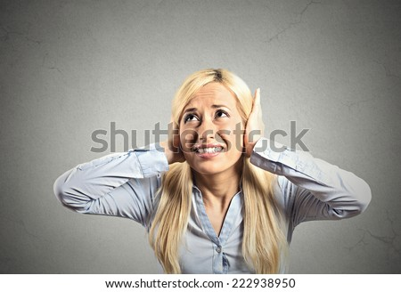 Portrait young annoyed, unhappy, stressed woman covering her ears, looking up, to say, stop making loud noise, giving me headache isolated grey background with copy space. Negative emotion reaction - stock photo
