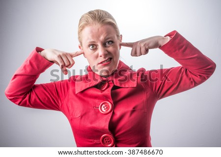 Portrait young annoyed, unhappy stressed woman covering her ears - Stop making loud noise its giving me a headache - stock photo