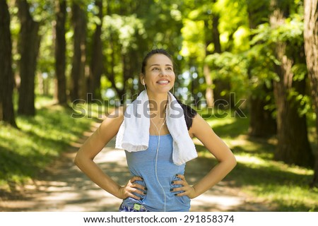 Portrait young attractive smiling fit woman with white towel resting after sport exercises outdoors on a background of park trees. Healthy lifestyle well being wellness concept  - stock photo