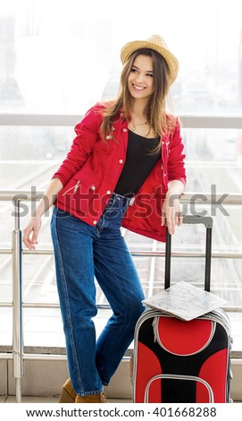 portrait young attractive woman in a red coat and hat standing in the terminal or at the station with a suitcase. The girl met on a trip. A woman looks off into the station hall - stock photo