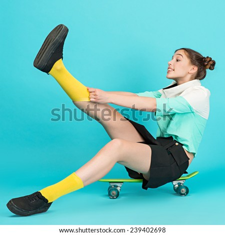 Portrait young beautiful sensual crazy girl posing on a blue background with a Longboard wearing a fashionable outfit, smiling pulls the yellow leggings - stock photo