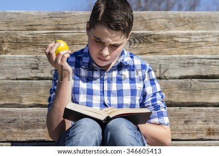 Portrait.Young boy reading a book in wooden stairs, summer