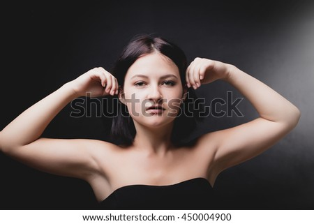 portrait young brunette woman on a black background - stock photo